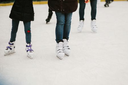 Skaters skating on iceskating ring in european city center in winter holidays.  Kids playing on white ice skating ring, healthy activity. Child legs in white skates Stock Photo