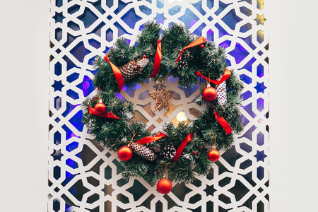 Traditional christmas wreath with red baubles ornaments and pine cones on modern white door in city center. Stylish christmas street decor  in european city. Winter holidays