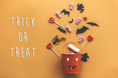 Trick or treat text sign. Happy Halloween. Jack o Lantern bucket with holiday candy, bats,spiders, skulls on orange paper, flat lay. Space for text. Seasons greeting card Stock Photo