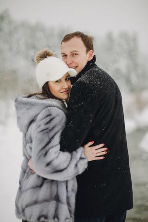 Stilvolles verliebtes Paar umarmt in schneebedeckten Bergen. Porträts der glücklichen Familie, die in den Winterbergen und im Wald sanft umarmt und lächelt. Gemeinsamer Urlaub