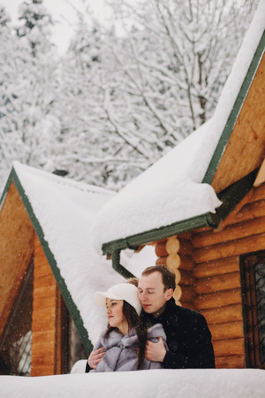 Stylish couple hugging in wooden cabin on background snowy woods in mountains. Happy family relaxing at cottage in winter mountains. Holiday getaway together. Space for text 写真素材