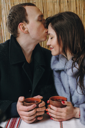 Stylish couple holding hot tea in cups and embracing and kissing on wooden porch in winter snowy mountains. Happy romantic family with drinks hugging. Holiday getaway together