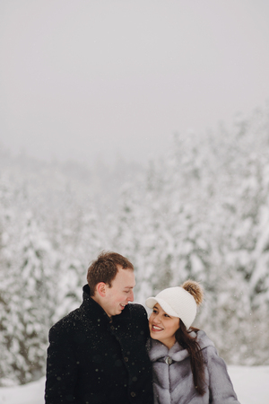 Stylish couple in love hugging in snowy mountains. Portraits of happy family gently embracing and smiling in winter mountains and forest. Holiday getaway together
