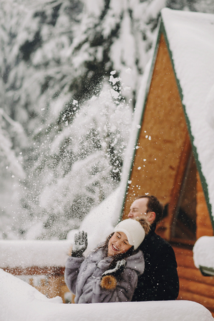 Stylish couple playing with snow in wooden cabin on background of winter snowy  mountains. Happy family having fun and smiling in snow at cottage. Holiday getaway together
