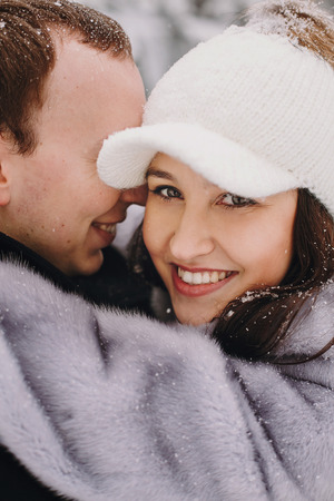 Stylish couple in love hugging in winter snowy mountains. Portraits of happy romantic man and woman smiling and embracing at waterfall in snow. Holiday getaway together.