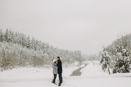 Stylish couple in love holding hands and embracing in snowy mountains. Happy family gently hugging and kissing in winter mountains and forest. Space for text