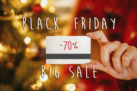 Black friday big sale text. 70 percent Holiday discount offer. Woman holding credit card on background of golden beautiful christmas tree with lights in festive room. Shopping