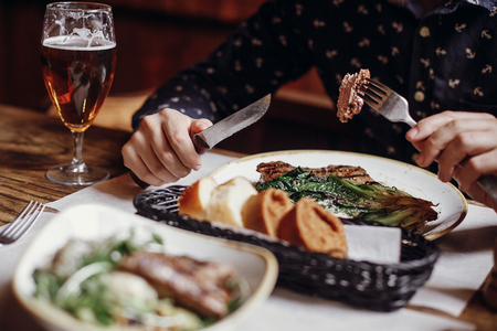 Man eating delicious juicy steak with grilled cabbage,tomatoes and cheese on table at cafe terrace in city street. Hands holding fork and knife and tasting bbq with vegetables in restaurant