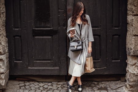Gorgeous young woman with cup of coffee and bag, smiling and standing at old wooden door in city street. Stylish happy hipster girl with beautiful hair and perfect smile shopping