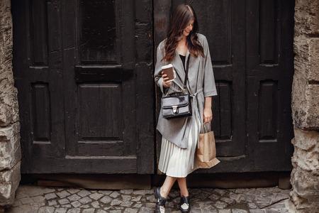 Hermosa mujer joven con una taza de café y una bolsa, sonriendo y de pie en la antigua puerta de madera en las calles de la ciudad. Chica elegante hipster feliz con un cabello hermoso y una sonrisa perfecta de compras