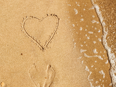 Heart written on sandy beach with wave near sea. Happy valentines day concept. Summer vacation and honeymoon for newlyweds. Hello summer. Space for text. Happy holidays