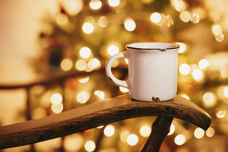 cozy winter holidays. warm atmospheric moment . mug with hot drink on old wooden chair on background of golden beautiful christmas tree with lights in festive room. Stock Photo