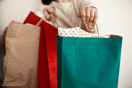 Black Friday. Christmas Sales. Happy Girl holding colorful shopping bags on white background. Space for text. Cyber Monday. Christmas Shopping and seasonal sale.