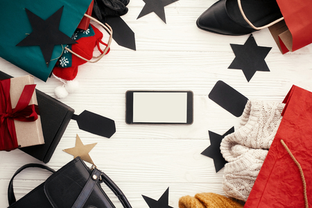 Christmas shopping and seasonal sale. Phone with empty screen, bags, clothes and shoes, gift boxes, tags on rustic wood. Space for text. Advertising app. Black Friday Stock fotó