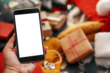 Hand holding phone with empty screen on background of credit cards and money in wallet, bags, clothes, gifts. Space for text. Advertising app. Christmas shopping and sale. Black friday Stock fotó