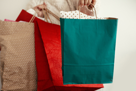 Christmas Shopping and seasonal sale. Happy Girl holding colorful shopping bags on white background. Christmas Sales. Space for text.  Black Friday. Cyber Monday