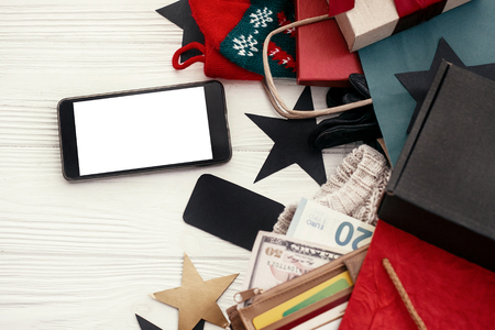 Christmas shopping and seasonal sale. Credit cards and money in wallet, phone with empty screen, bags, clothes, gift boxes, tags on rustic wood. Space for text. Advertising app Stock fotó