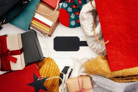 Christmas shopping and seasonal sale. Credit cards, money, wallet,  bags, clothes, gift boxes on rustic wood. Empty black tag with Space for text. Advertising concept.  Seasonal sales