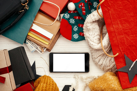 Credit cards and money in wallet, phone with empty screen, paper bags with clothes, gift boxes on rustic wood. Christmas shopping and seasonal sale. Advertising app.  Black Friday