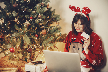 beautiful girl in reindeer antlers holding credit card and shopping online, sitting with laptop at golden beautiful christmas tree with lights and presents in festive room. christmas sales