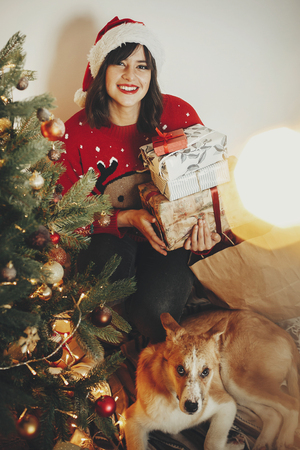 happy girl in santa hat holding gift boxes and cute dog sitting at golden beautiful christmas tree with lights and presents in festive room. family happy atmospheric   moments. holidays