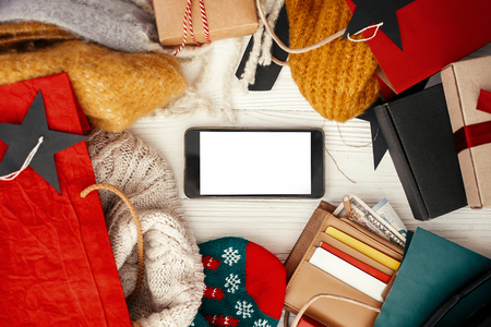 Phone with empty screen, credit cards, money, wallet,  bags, clothes, gift boxes, tags on rustic wood. Space for text. Advertising app. Christmas shopping and seasonal sale.