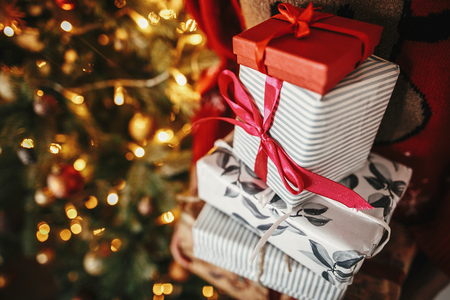 many Christmas gift boxes in hands at golden beautiful christmas tree with lights in festive room. winter holiday atmospheric moments. seasons greetings. Merry Christmas