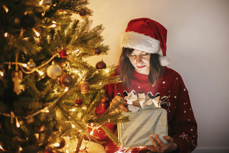 Merry Christmas. happy girl in santa hat opening magic Christmas gift box at golden beautiful christmas tree with lights and presents in festive room. winter atmospheric  moments Stock fotó