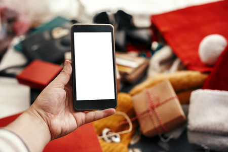 Christmas shopping and sale. Hand holding phone with empty screen on background of credit cards,money, wallet, bags, clothes, gifts, jewelry. Space for text. Advertising app. Black Friday