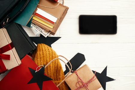 Christmas shopping and seasonal sale. Phone with empty screen, credit cards, money, wallet,  bags, clothes, gift boxes, tags on rustic wood. Space for text. Advertising app