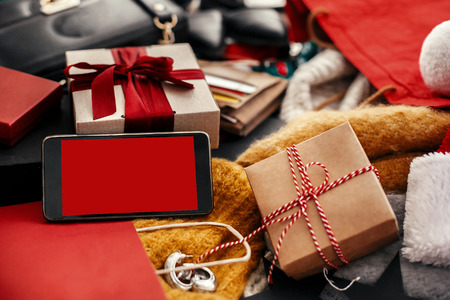 Phone with empty screen, credit cards, money, wallet, bags, clothes, gift boxes, jewelry on rustic wood. Space for text. Advertising  app concept. Christmas shopping and seasonal sale.