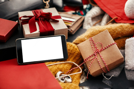 Christmas shopping and seasonal sale. Phone with empty screen, credit cards, money, wallet, bags, clothes, gift boxes, jewelry on rustic wood. Space for text. Advertising app concept