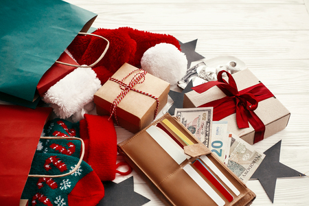 Christmas  shopping and sales concept. Credit cards and money in wallet, paper bags with clothes, stockings, gift boxes, jewelry on white rustic background. Seasonal advertising and sale