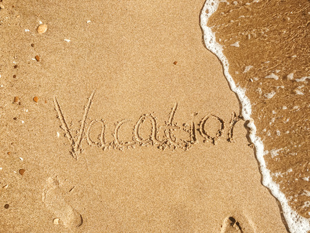 Vacation text written on sandy beach with wave near sea. Summer vacation concept. Hello summer. Travel and wanderlust. Space for text. Happy holidays. Time to relax