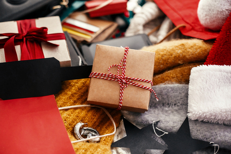 Christmas shopping and seasonal sale. Gift box with empty black tag, credit cards, money, wallet, bags, clothes, jewelry on rustic wood. Space for text. Advertising concept. black friday