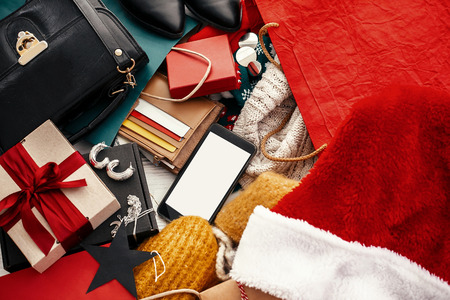 Christmas shopping and seasonal sale. Phone with empty screen, credit cards, money, wallet, bags, clothes, gift boxes, jewelry on rustic wood. Space for text. Advertising concept