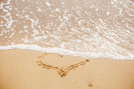 Heart written on sandy beach with wave near sea. Love concept. Happy valentines day.  Honeymoon for newlyweds. Valentine day. Space for text. Happy holidays. Broken heart