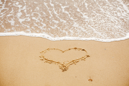 Heart written on sandy beach with wave near sea. Love concept. Happy valentines day.  Honeymoon for newlyweds. Valentine day. Space for text. Happy holidays