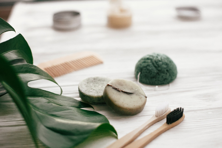 Zero waste solid shampoo bar, bamboo toothbrushes, wooden brush and konjaku sponge on white wood with green monstera leaves. Eco friendly natural products plastic free Reklamní fotografie