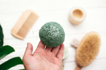 Hand holding natural konjaku sponge on background of bamboo brush, deodorant in glass on white wood with green monstera leaves. Zero waste concept. Choose plastic free eco products