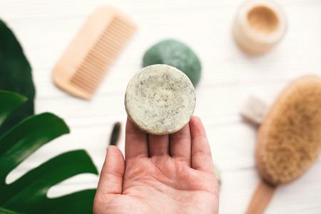 Hand, die eine natürliche feste Shampoobar auf dem Hintergrund von Bambusbürste, Deodorant, Schwamm auf weißem Holz mit grünen Monsterablättern hält. Kein Verlust. Auswahl an plastikfreien Ökoprodukten
