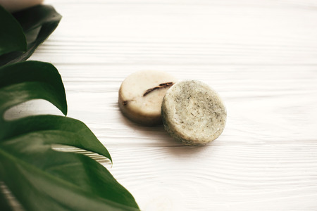 Natural eco friendly solid shampoo bar, green conditioner, soap on white wood with green monstera leaves. Eco products plastic free. Hair care and treatment. Zero waste concept.