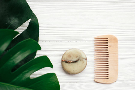 Natural eco friendly solid shampoo bar, wooden brush,  green  conditioner, soap on white wood with green monstera leaves.  Eco products plastic free. Zero waste. Hair care Фото со стока