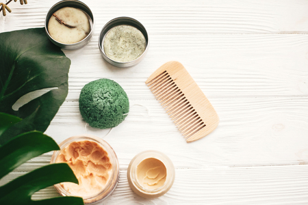 Natural eco friendly solid shampoo bar, wooden brush,  deodorant cream, scrub and konjaku sponge on white wood with green monstera leaves. Zero waste products plastic free