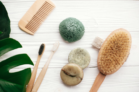 Zero waste flat lay. Natural solid shampoo bar, bamboo toothbrushes, wooden brush,  deodorant cream and konjaku sponge on white wood with green monstera leaves. Eco products plastic free Stockfoto