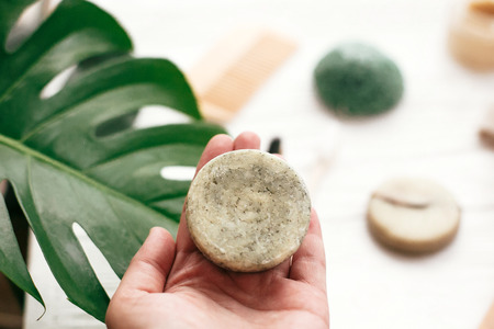 Cero desperdicio. Elección de productos ecológicos sin plástico. Mano que sostiene la barra de champú sólido natural sobre fondo de cepillo de bambú, desodorante, esponja en madera blanca con hojas verdes de monstera.