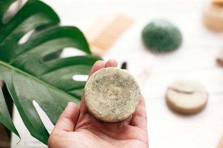 Zero sprechi. Prodotti ecologici senza plastica di prima scelta. Mano che tiene la barra di shampoo solido naturale sullo sfondo di una spazzola di bambù, deodorante, spugna su legno bianco con foglie di monstera verde.