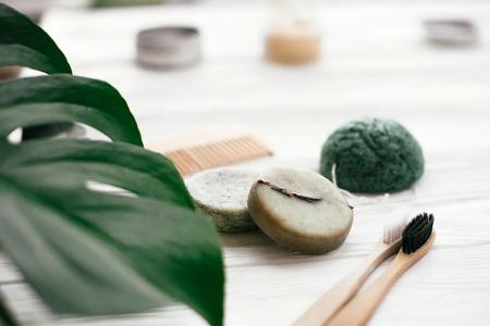 Zero waste solidny szampon, bambusowe szczoteczki do zębów, drewniana szczotka i gąbka konjaku na białym drewnie z zielonymi liśćmi monstery. Ekologiczne produkty naturalne bez plastiku