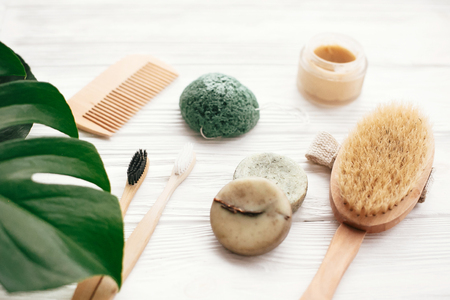 Zero waste solid shampoo bar, bamboo toothbrushes, wooden brush, natural deodorant and konjaku sponge on white wood with green monstera leaves. Eco  natural products plastic free