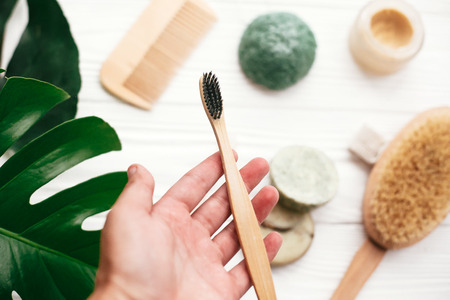 Hand holding natural bamboo toothbrush on background of shampoo bar, brush, toothpaste on white wood with green monstera leaves. Zero waste. Choose plastic free eco products